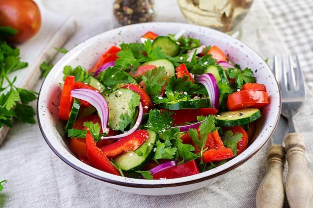 Sałatka pomidorowo-ogórkowa z czerwoną cebulą, papryką, czarnym pieprzem i natką pietruszki. wegańskie jedzenie. menu dietetyczne.