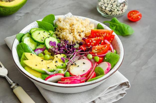 Sałatka quinoa ze świeżymi warzywami, szpinakiem, zielonym groszkiem, mikrogreenami i sezamem w misce na betonowym tle. koncepcja zdrowej żywności.