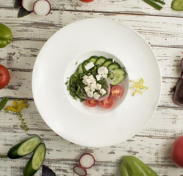 Sałatka roka z serem feto, posiekanym ogórkiem, pomidorami i zielenią.