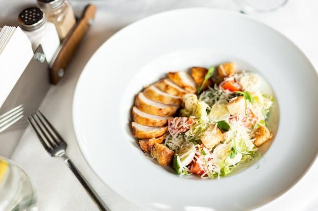 Sałatka romain z grillowanym kurczakiem, grzankami czosnkowymi i parmezanem podawana na białym talerzu na stole z białym obrusem, sprzętem i lampką wina w restauracji