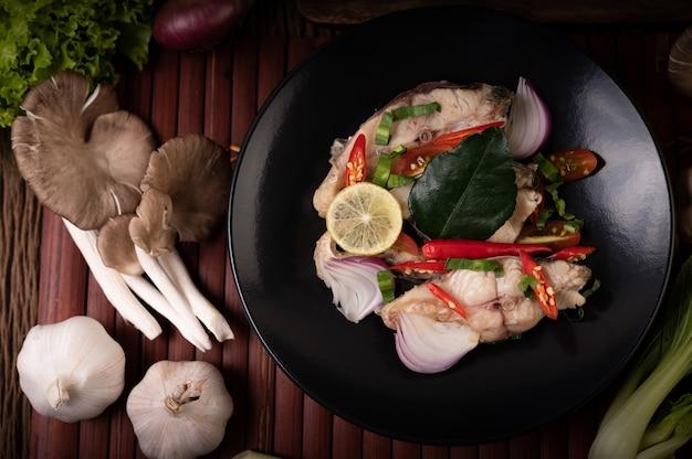 Sałatka rybna z limonką, chili, trawą cytrynową, cebulą, czerwoną cebulą, natką pietruszki i liśćmi limonki kaffir na talerzu
