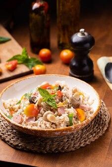 Sałatka ryżowa w misce na zalesionym stole z bliska