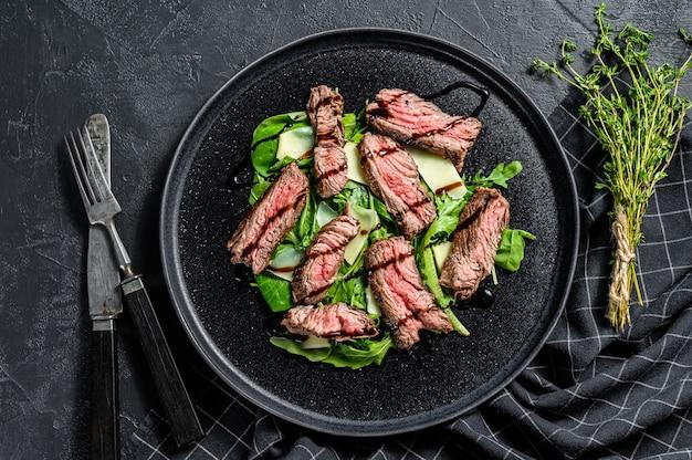 Sałatka stek ze szpinakiem, rukolą i pokrojoną wołowiną. widok z góry