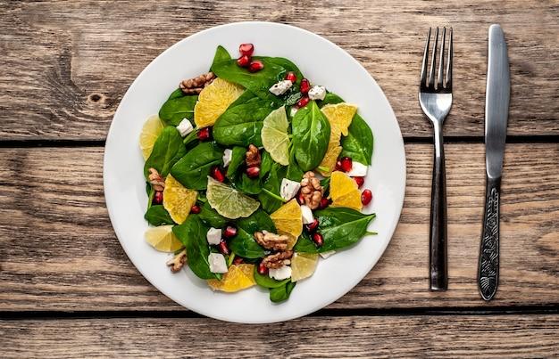 Sałatka szpinakowa, pomarańcza, cytryna, granat, ser feto, orzech na białym talerzu na drewnianym stole