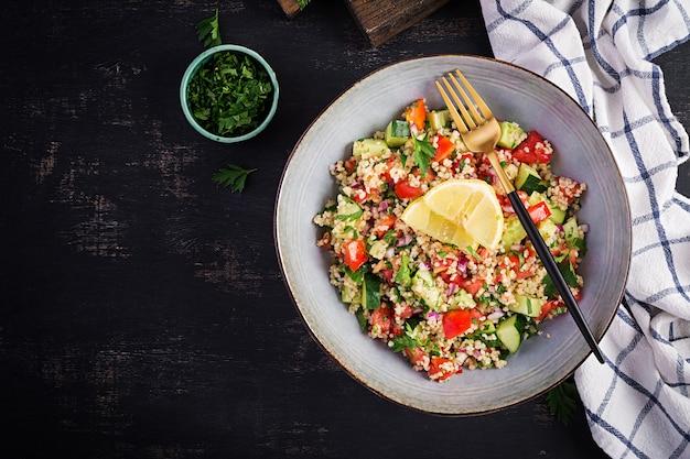 Sałatka tabbouleh. tradycyjne danie bliskowschodnie lub arabskie. sałatka wegetariańska lewantyńska z pietruszką, miętą, kaszą bulgur, pomidorem. widok z góry