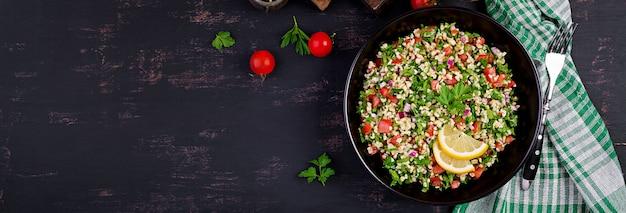 Sałatka tabbouleh. tradycyjne danie bliskowschodnie lub arabskie. sałatka wegetariańska z lewantyny z natką pietruszki, miętą, bulgur, pomidorem. transparent.