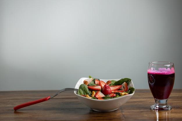 Sałatka truskawkowa i szpinakowa z sokiem buraczanym na drewnianym stole