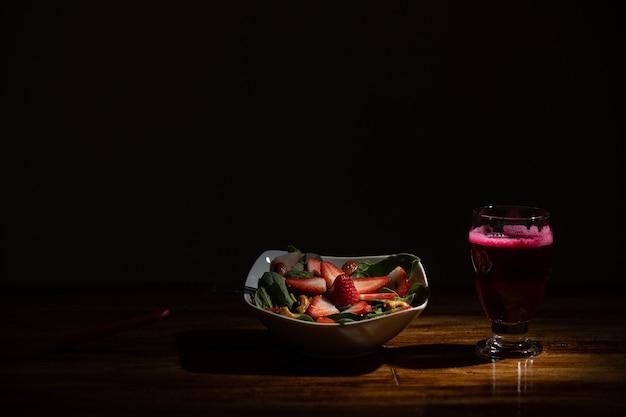 Sałatka truskawkowo-szpinakowa z sokiem buraczanym na ciemnej powierzchni