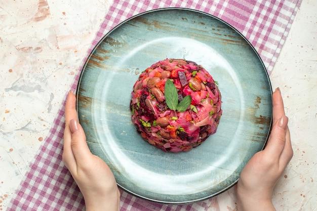 Sałatka vinaigrette z widokiem z góry na cyjanowym owalnym talerzu w kobiecej dłoni fioletowy biały obrus w kratkę na jasnoszarym stole