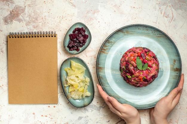 Sałatka vinaigrette z widokiem z góry na owalnym talerzu w ręcznie ciętym buraku i innych rzeczach w miskach na jasnoszarym stole