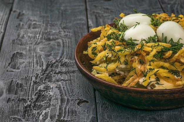 Sałatka w formie gniazda z jajkami przepiórczymi w głębokiej misce na drewnianym stole