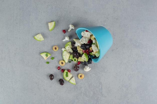 Sałatka w niebieskim kubku z mieszanką pokrojonych warzyw i owoców.
