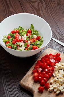 Sałatka warzywna. pomidory czereśniowe z serem sałatkowym na desce do krojenia, biała miska ze składnikami żywności