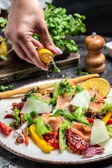 Sałatka warzywna. pyszna zdrowa sałatka warzywna z sałatą rybną z łososia, suszonymi pomidorami i ziołami. zamrozić ruch splash krople soku z cytryny, koncepcja zdrowego odżywiania, smaczny obiad