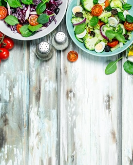 Sałatka warzywna. różnorodne ekologiczne sałatki, warzywa z oliwą i przyprawami. na rustykalnym tle.