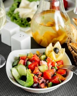 Sałatka warzywna w misce z cytryną i czarnymi oliwkami.