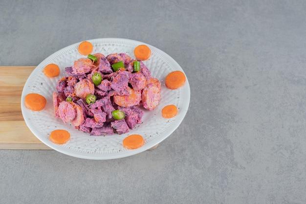 Sałatka warzywna z buraczkami fioletowymi i posiekaną marchewką w pomarańczy zmieszana z kwaśną śmietaną.
