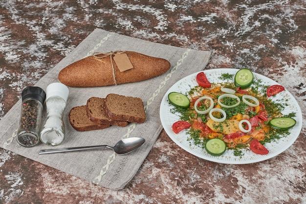 Sałatka warzywna z kromkami chleba.