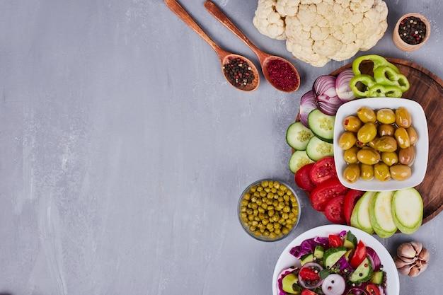 Sałatka warzywna z pokrojonymi w plasterki i posiekanymi potrawami oraz innymi przekąskami dookoła.