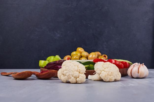 Sałatka warzywna z pokrojonymi w plasterki i posiekanymi potrawami oraz marynowanymi oliwkami.
