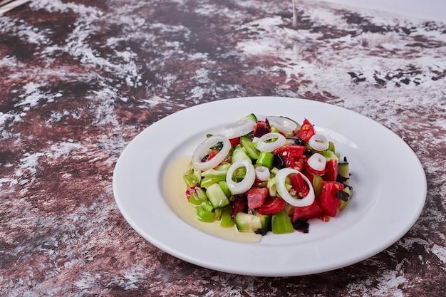 Sałatka warzywna z posiekanymi i mielonymi składnikami na białym talerzu, kąt widzenia.