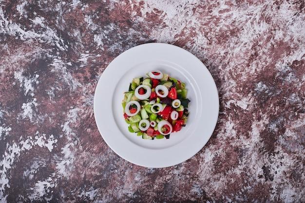 Sałatka warzywna z posiekanymi i mielonymi składnikami zmieszanymi z olejem, widok z góry.