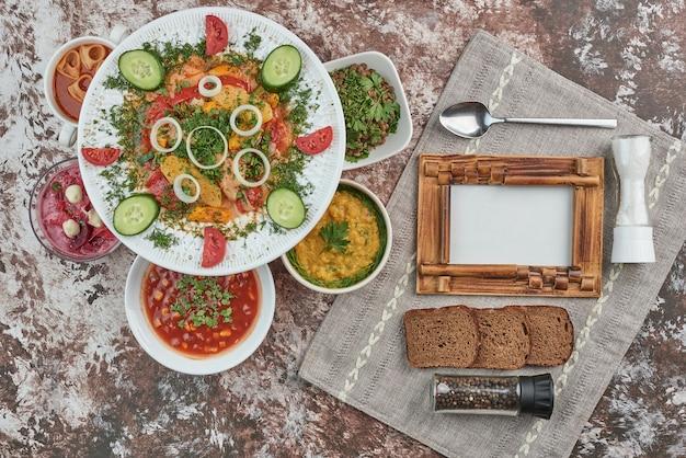 Sałatka warzywna z potrawami w naczyniach ceramicznych.