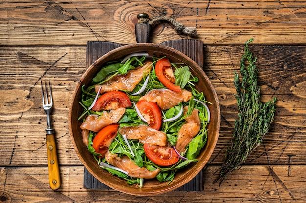 Sałatka warzywna z wędzonym łososiem, rukolą, pomidorem i zielonymi warzywami. drewniany stół. widok z góry.
