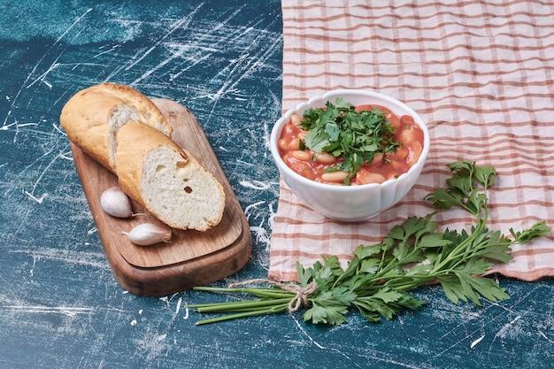 Sałatka warzywna z ziołami i przyprawami podawana z bagietką.