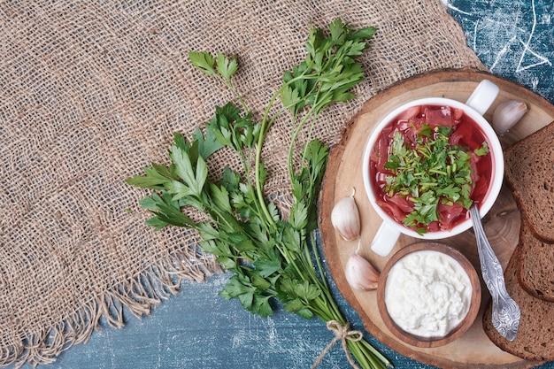 Sałatka warzywna z ziołami i przyprawami podawana z jogurtem i ciemnym pieczywem.