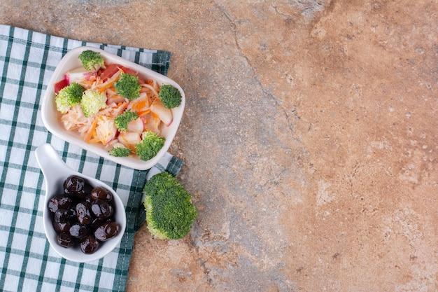Sałatka warzywno-owocowa w białym talerzu z czarnymi oliwkami