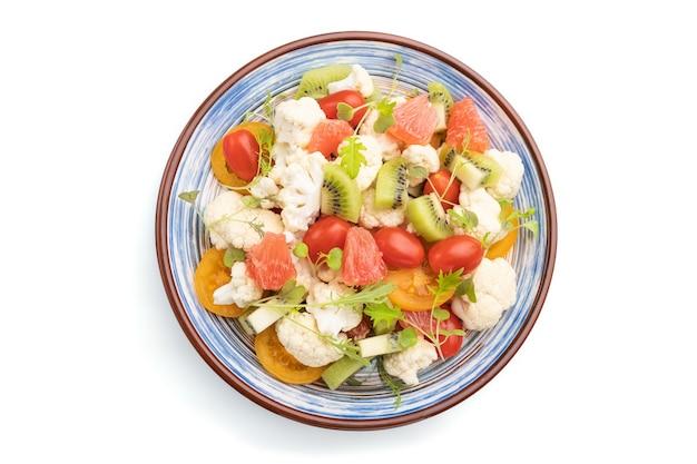 Sałatka wegetariańska kapusta kalafior, kiwi, pomidory, mikrogreen kiełki białym tle widok z góry,