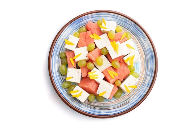 Sałatka wegetariańska z arbuzem, serem feta i winogronami na niebieskim talerzu ceramicznym na białym tle. widok z góry, zbliżenie, płaski układ.