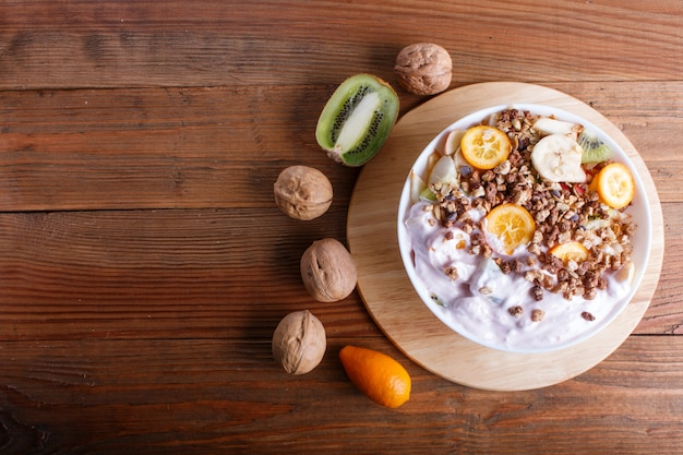 Sałatka wegetariańska z bananami, jabłkami, gruszkami, kumkwatami, kiwi z muesli i jogurtem na brązowym drewnie