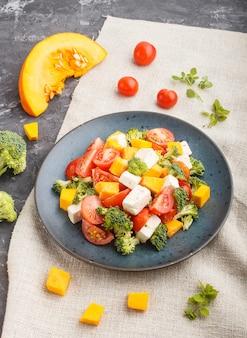 Sałatka wegetariańska z pomidorami brokuł, serem feta i dynią na niebieskim talerzu ceramicznym na czarnym tle betonowym
