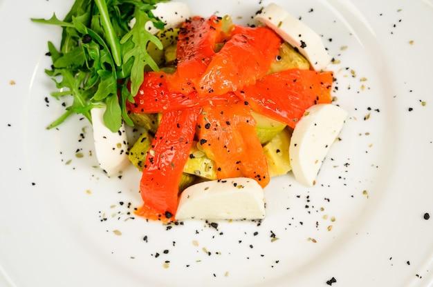 Sałatka wegetariańska z pomidorami, papryką i cebulą na drewnianym stole. zdrowa sałatka ze świeżymi dojrzałymi warzywami letnimi