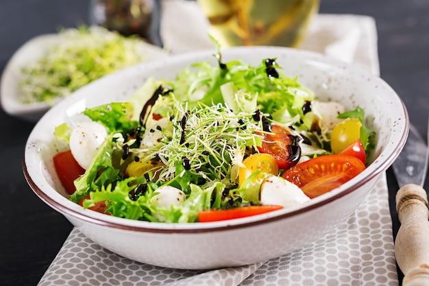 Sałatka wegetariańska z pomidorkami cherry, mozzarellą i sałatą.