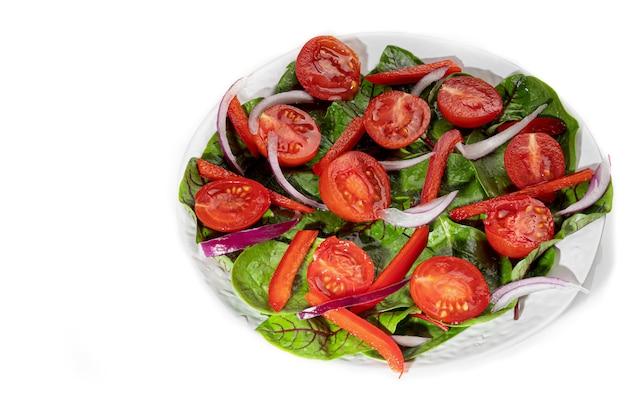 Sałatka wegetariańska z pomidorkami koktajlowymi, szpinakiem, czerwoną cebulą i papryką z masłem. na białym tle. izolować. skopiuj miejsce.