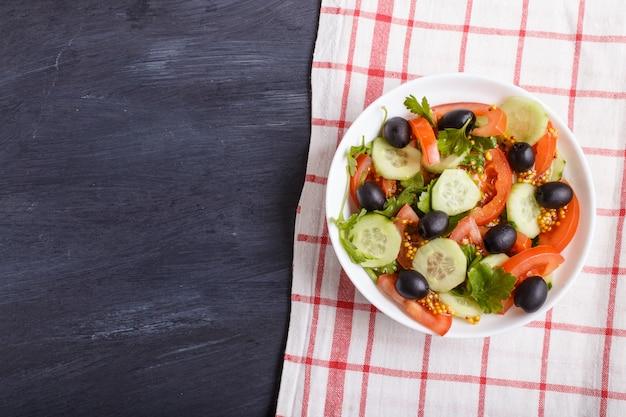 Sałatka wegetariańska z pomidorów, ogórków, pietruszki, oliwek i musztardy na lnianym obrusie.
