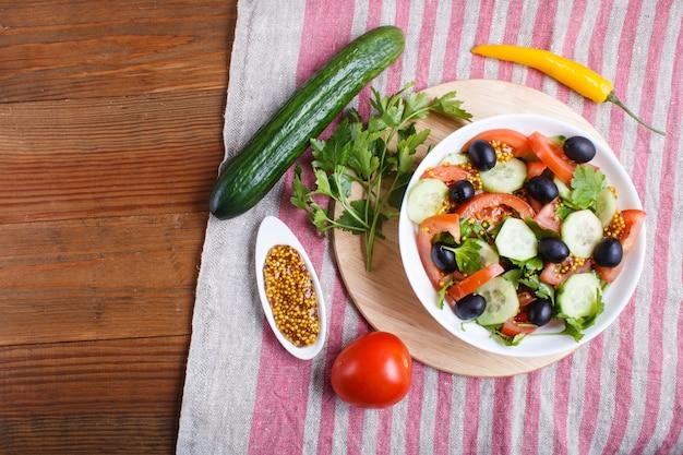 Sałatka wegetariańska z pomidorów, ogórków, pietruszki, oliwek i musztardy na lnianym obrusie