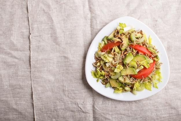 Sałatka wegetariańska z selera, kiełkującego żyta, pomidorów i awokado na lnianym obrusie, widok z góry.
