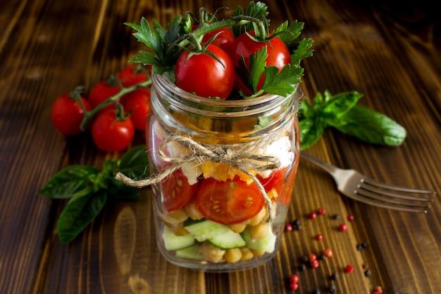 Sałatka wegetariańska z warzywami i ciecierzycą w szklanym słoju na brązowym tle drewniane