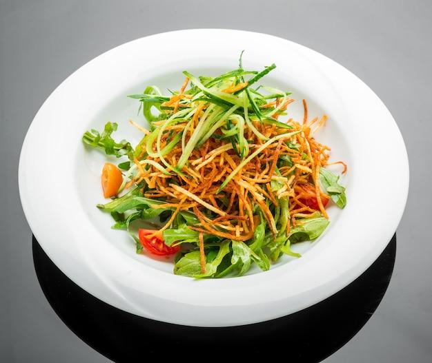 Sałatka wegetariańska ze smażonymi frytkami i rukolą na talerzu