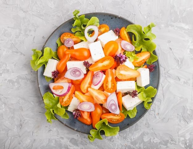 Sałatka wegetariańska ze świeżych pomidorów winogronowych, sera feta, sałaty i cebuli, widok z góry.