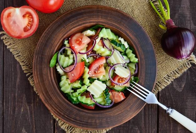 Sałatka witaminowa z ogórkami, pomidorami, fioletową cebulą i serem w glinianej misce na drewnianym stole. widok z góry