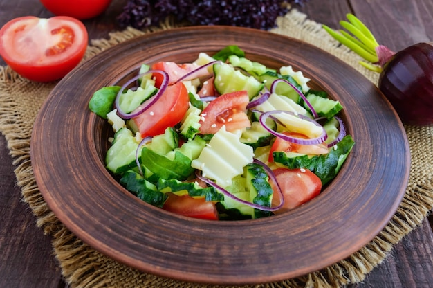Sałatka witaminowa z ogórkami, pomidorami, fioletową cebulą i serem w glinianej misce na drewnianym stole