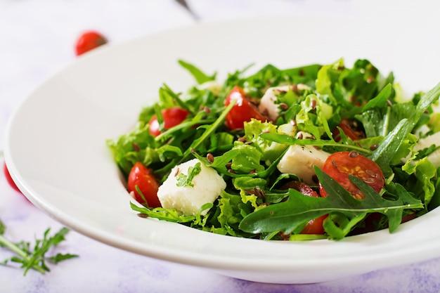 Sałatka witaminowa ze świeżych pomidorów, ziół, sera feta i nasion lnu. menu dietetyczne. odpowiednie odżywianie.