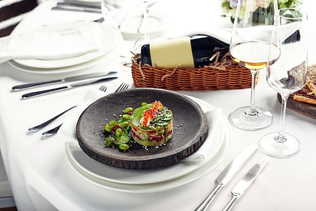 Sałatka z awokado, owoców morza, mięsa, warzyw i pestek dyni. dietetyczne, pełnowartościowe i smaczne. uroczyste dania bankietowe. menu restauracji dla smakoszy. białe tło.
