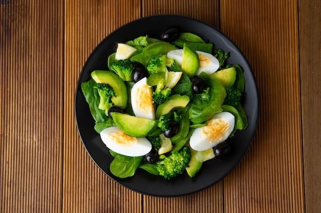 Sałatka z awokado z brokułami, szpinakiem, oliwkami i gotowanymi jajkami w czarnym talerzu, drewniany stół.