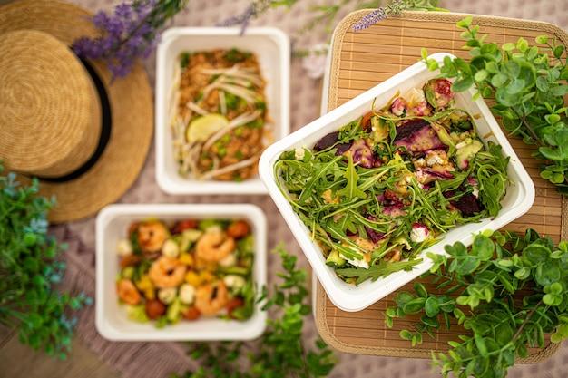 Sałatka z burakiem rukolowym i serem feta. jedzenie wegetariańskie. sałatka z krewetek i azjatycki pad thai. pozycja z naturalnym wystrojem. koncepcja dostawy żywności